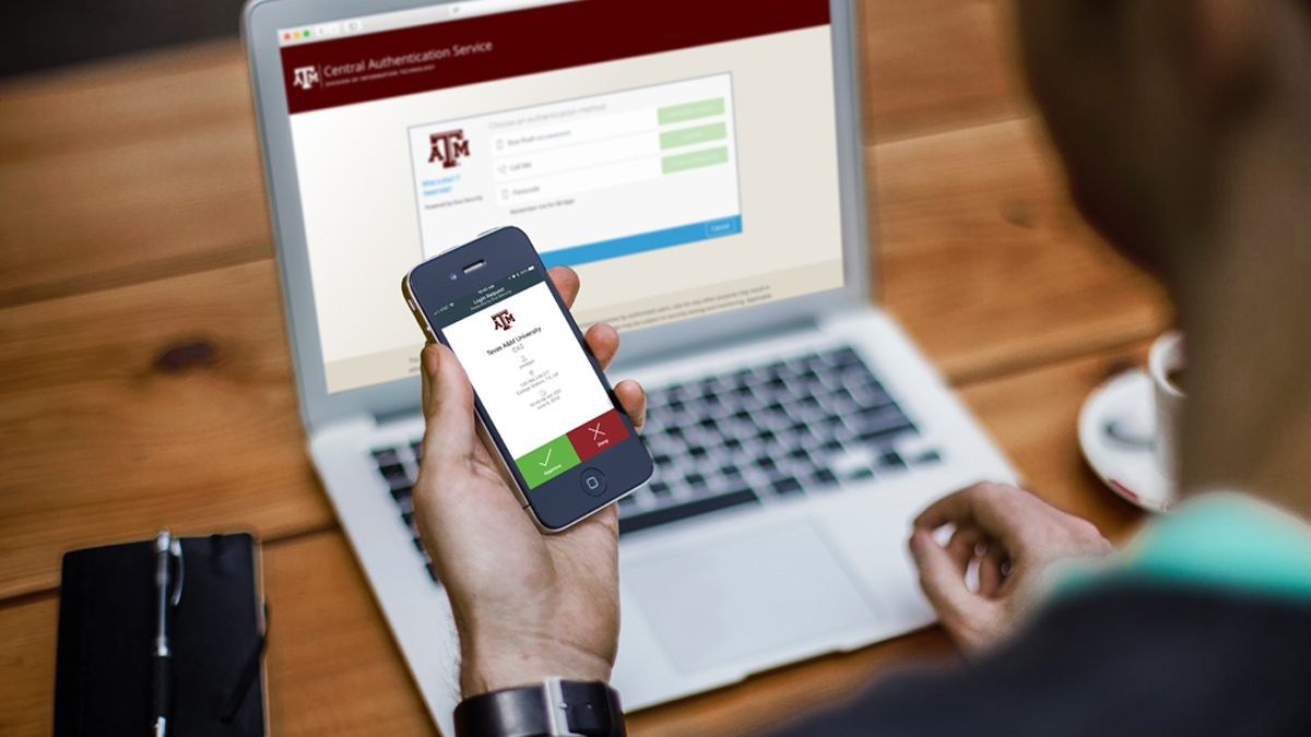 Student holds up his phone to the Duo app as he signs into a secure Texas A&M site.