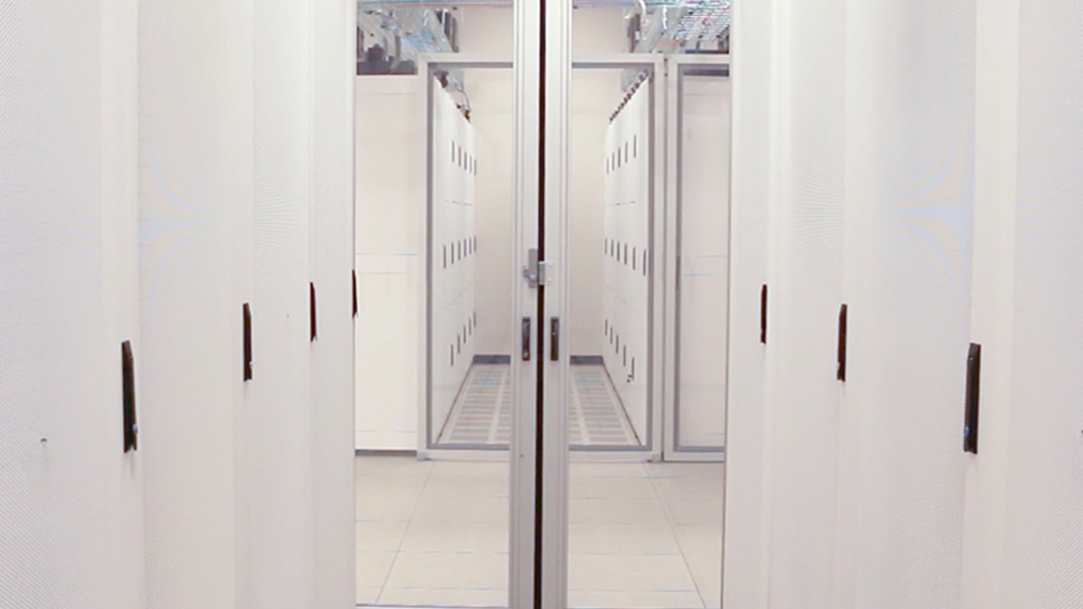 White racks of servers protected by locking glass doors inside a campus data center.