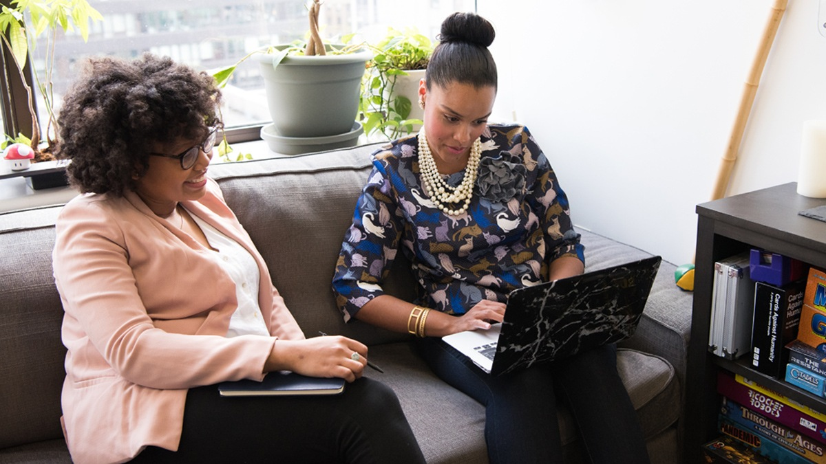 Two women engaged in discussion while looking at a laptop.
